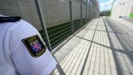 Ein Justizbeamter steht an den Sicherheitszäunen der Justizvollzugsanstalt Frankfurt (Symbolbild).