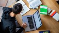 Ein Student organisiert sein Studium vom Wohnzimmer der Eltern aus.