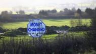 Straßenschild in einer Hecke an der Grenze zwischen Nordirland und der Republik Irland