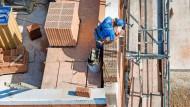 Ein Bauarbeiter steht auf einer Baustelle und mauert eine Wand. Die Zahl der Baugenehmigungen in Baden-Württemberg hat 2021 im ersten Halbjahr stark zugenommen.