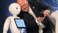 Arne Schönbohm, Präsident des Bundesamtes für Sicherheit in der Informationstechnik, macht ein Selfie mit einem Roboter.