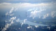 Kühltürme mit Wasserdampf-Wolken: Betreiber von Industrieanlagen wie dieser von Thyssen-Krupp in Essen müssen für jede ausgestoßene Tonne CO2 ein Zertifikat erwerben.