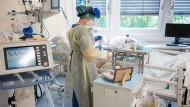 Eine Krankenpflegerin in Schutzausrüstung (PSA) am Bett eines Corona-Patienten auf der Isolierstation für Corona-Patienten der Asklepios Klinik in Langen.