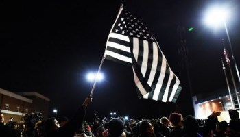 A protester waving a black-and-white American flag in Ferguson, Missouri, last night