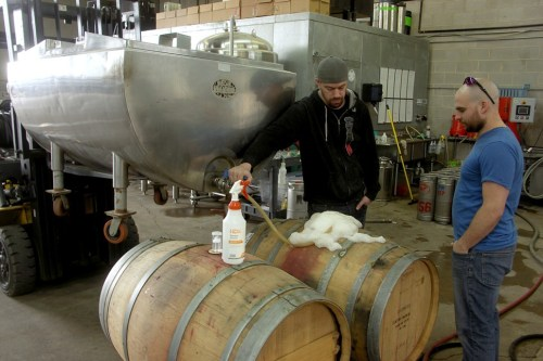 Slapshot cofounder Steven Miller and Vice District brewer Mike Kristin transfer a spontaneously fermented collaboration by Slapshot, Mikerphone, and Transient Artisan Ales from a jury-rigged coolship to a wine barrel.