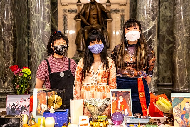 Organizers Anny Chen, Lena Chen, and Caroline Yoo stand behind an altar where people brought offers for victims of the Atlanta shooting during an event in support of Asian American and Pacific Island women and sex workers at the Carnegie Museum of Art on April 1. - CP PHOTO: KAYCEE ORWIG