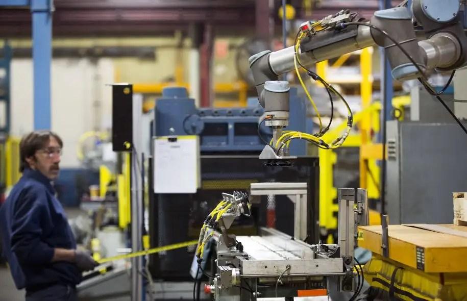 À l'usine de l'entreprise Etalex, à Anjou, un employé travaille à proximité d'un robot.
