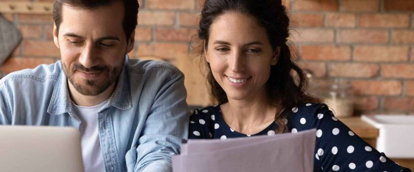 Happy young married couple looking at loan, mortgage agreement, analyzing rate schedule, planning costs and family budget.  Man and woman use laptop and read documents together