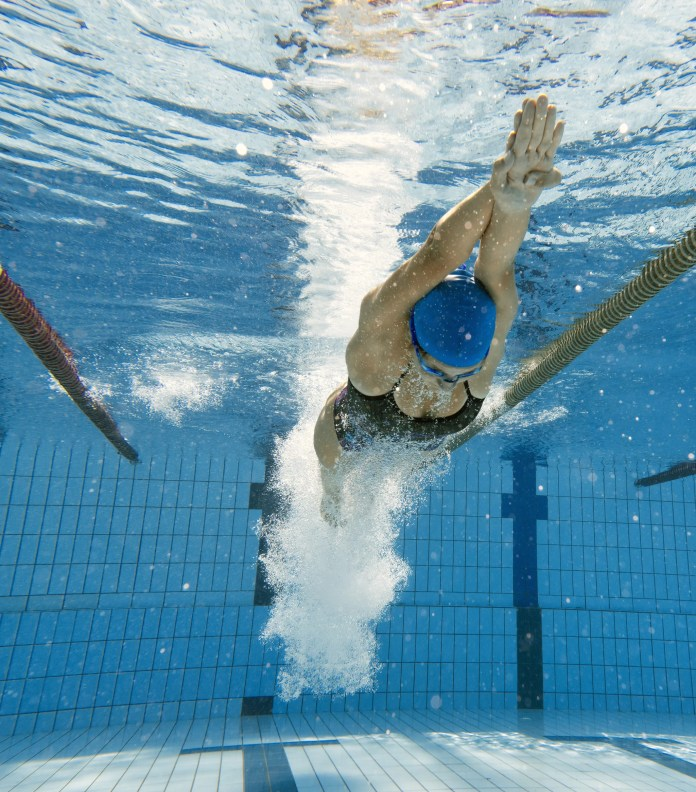 Young female swimmer diving in the pool
