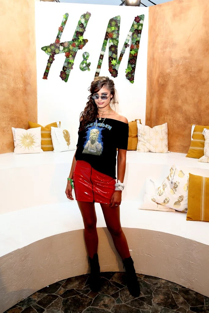 Taylor Hill wearing a leather mini skirt and off-the-shoulder graphic tee at the H&M Loves Coachella tent.
