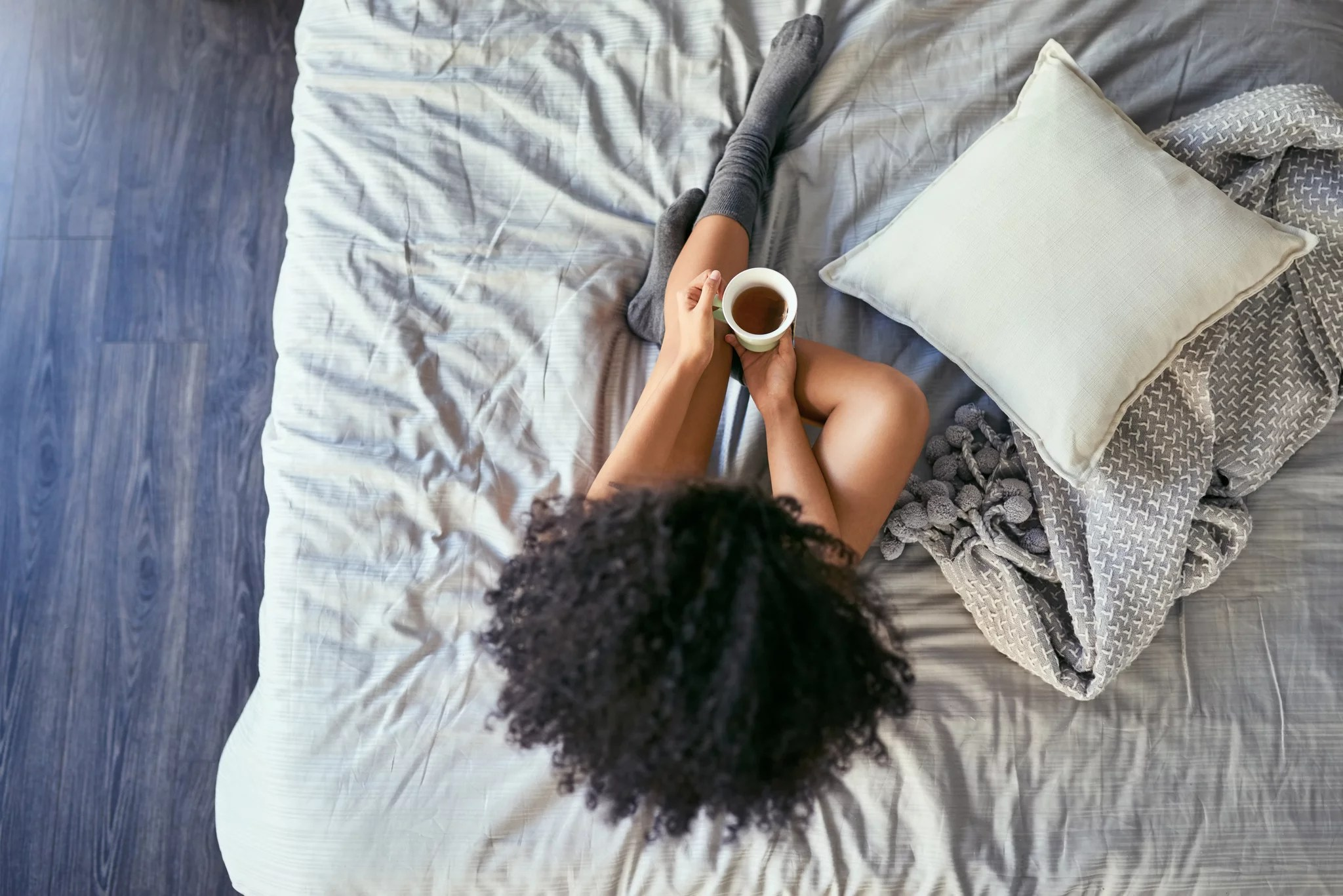 High angle shot of a young woman relaxing on her bed in the morning and drinking tea