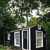 The shed's dark exterior juxtaposes its light and airy interiors.  Source: Cody Ulrich via Homepolish