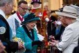 La regina Elizabeth passare il suo giorno che distribuisce con indifferenza le borse di soldi alla gente