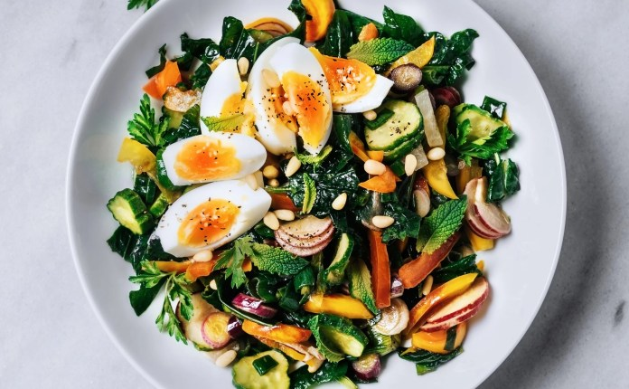 A bowl of fresh salad with boiled eggs on a white background