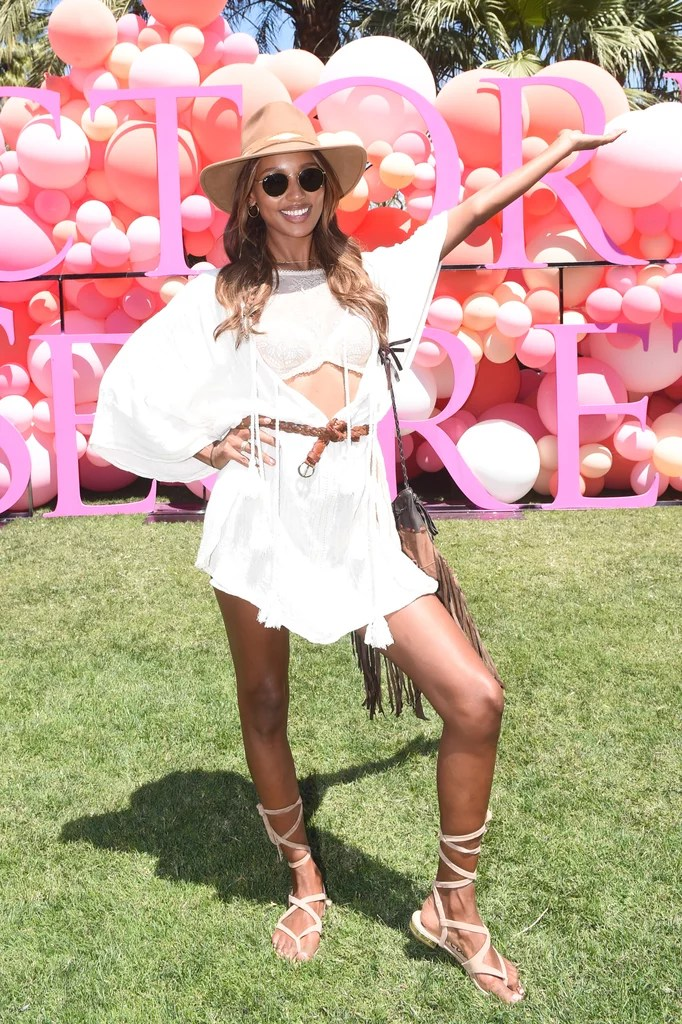 Jasmine Tookes wearing a belted caftan, crop top, and gladiator sandals at the Victoria's Secret Angel Oasis.