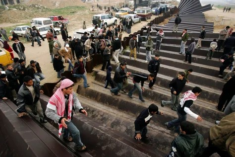 Image: Palestinians cross the Rafah border into Egypt.