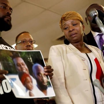 Image: Lesley McSpadden, right, the mother of 18-year-old Michael Brown, watches as Brown's father, Michael Brown Sr., holds up a family picture of himself, his son, top left in photo, and a young child during a news conference