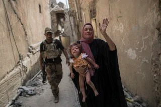 Image: A woman holds a young injured girl in the Old City of Mosul