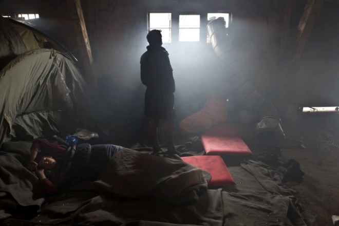 An Afghan refugee sleeps on the ground while another looks out a window in an abandoned warehouse where they and other migrants took refuge in Belgrade, Serbia, on Feb. 1, 2017.
