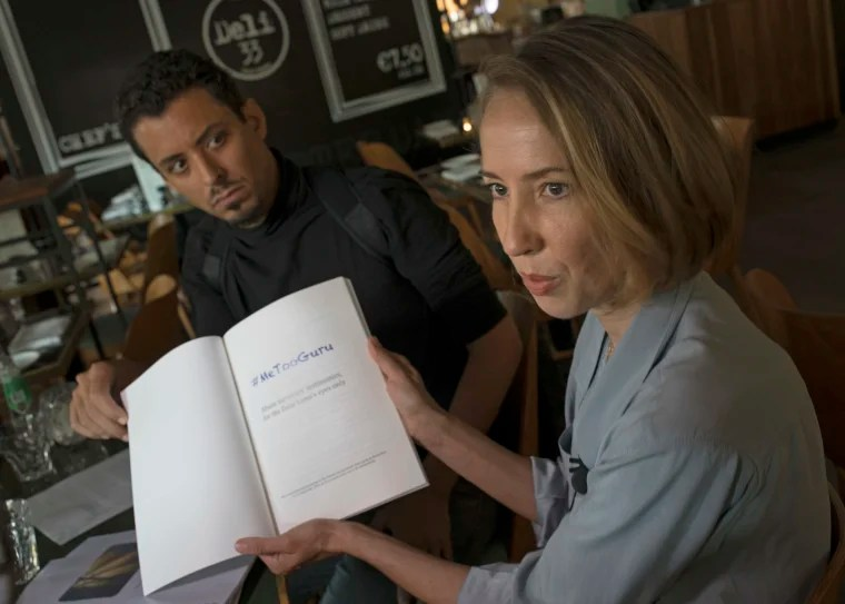 Image: Ricardo Mendes, left, and Oane Bijlsma, two of four alleged victims of sexual, physical and psychological abuse show the report titled they presented the Dalai Lama.