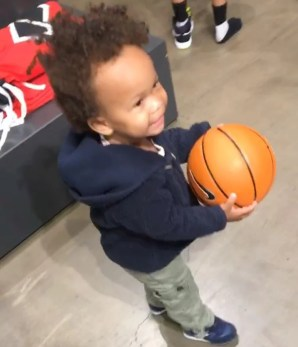 Joel Stallworth and TaMiya Dickerson's son Sammy holds a basketball they purchased at Santa Monica Place.