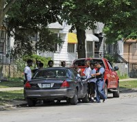 By law, police need to have a reason to formally stop someone. Here officers stop several men after a 2011 south-side shooting.