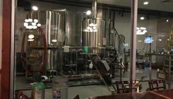 The brewing equipment, with ghostly reflections from the dining-room chandeliers