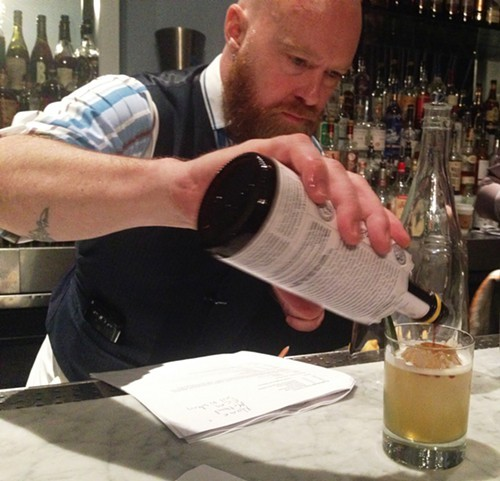 Toby Maloney adds a dash of Angostura bitters to a Tradewinds cocktail