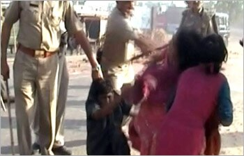 A senior police officer knocked an elderly woman down with his baton in Aligarh.