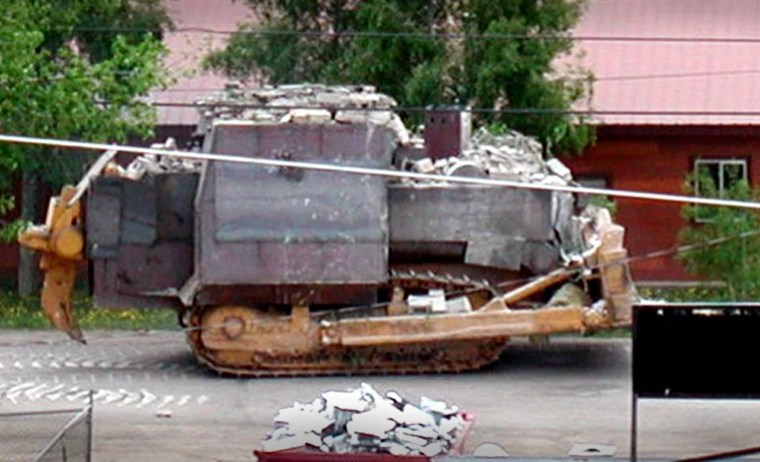 Marvin Heemeyer's bulldozer as it crosses a street. The armored plates are clearly visible and there is rubble from the destroyed buildings on the bulldozer's roof.