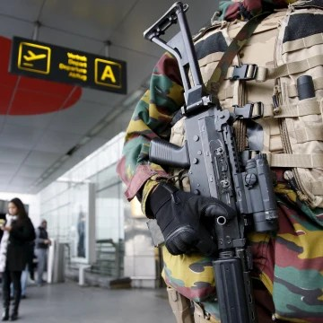 Image: A Belgian soldier stands guard at the entrance of Zaventem international airport near Brussels
