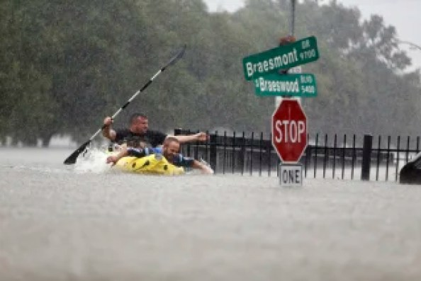 Image: Two kayakers try to beat the current pushing them down an overflowing Brays Bayou along S. Braeswood in Houston, T