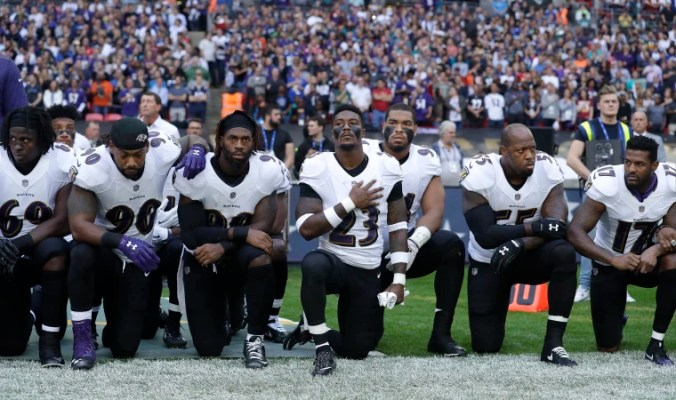 Image: Baltimore Ravens players kneel down during the playing of the U.S. national anthem before an NFL football game