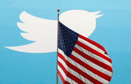 Image: The Twitter Inc. logo is shown with the U.S. flag during the company's IPO on the floor of the New York Stock Exchange in New York