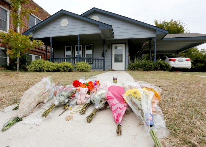 Flowers lie on the sidewalk in front of the house in Fort Worth, Texas on Oct. 14, 2019, where a white Fort Worth police officer shot and killed Atatiana Jefferson, a black woman, through a back window of her home.