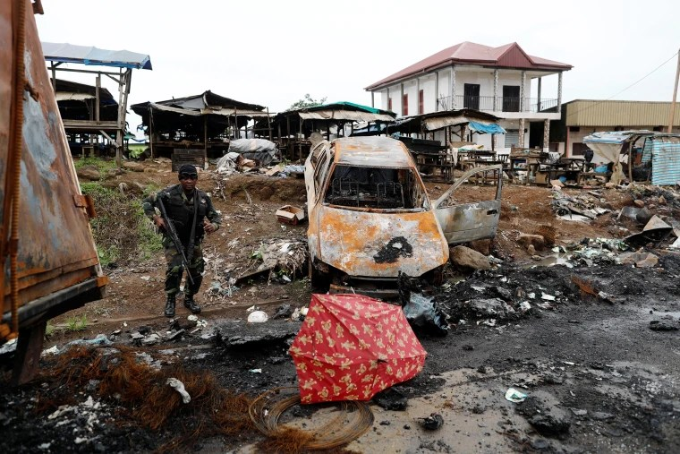 A Cameroonian elite Rapid Intervention Battalion (BIR) member walks past a burnt car while patroling in the city of  Buea in the anglophone southwest region, Cameroon
