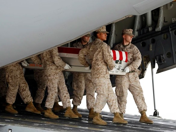 A Marine carry team, carries the transfer case containing the remains of Marine Lance Cpl. Jeremiah M. Collins Jr. of Milwaukee, Wis., upon arrival at...