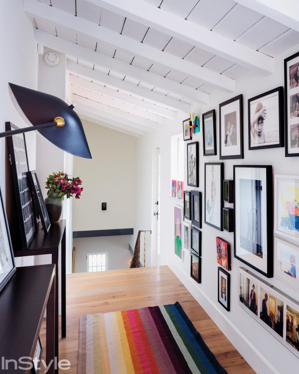 In Upstairs Hallway Wall Filled With Framed Artwork