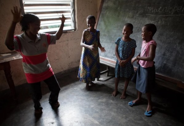 """A psychologist working for the NGO """"Amici Di Bambini"""" (Children's Friends) gestures towards children who have been rejected by their families after being accused of witchcraft"""