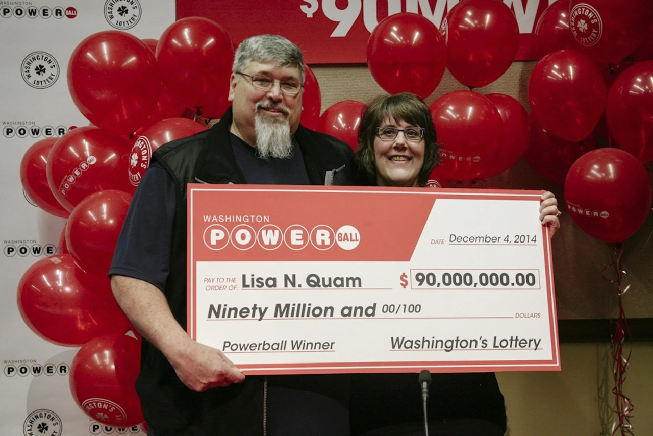 Image: Lisa Quam and her husband hold a check for $90 million during a news conference in Olympia, Washington