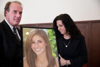 Image: Jim Burk, left, and Viviane Guerschon, right, hold a portrait of their daughter Lauren Burk