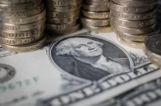 Image: Pound coins site beside dollar bills