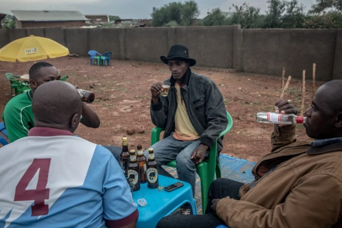 Image: Men drink beer and spirits in a bar in Nakivale refugee settlement in southwest Uganda.