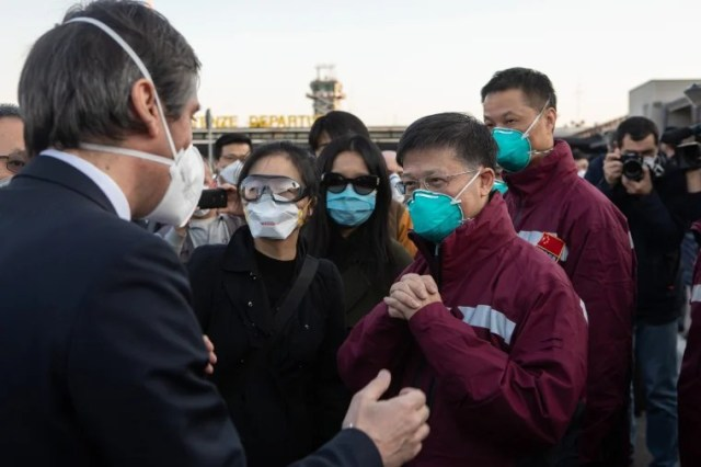 Image: Vice President of Lombardy Region Fabrizio Sala talks to a member of a Chinese Anti-Epidemic medical expert team pose for a photograph after landing at Milan - Malpensa airport