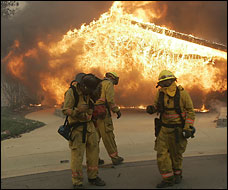 A wildfire driven by powerful Santa Ana winds threatens Pepperdine University and forces the evacuation of hundreds of homes in the Malibu Hills.