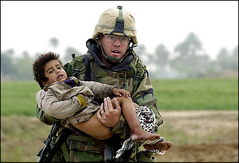 In March 2003, photographer Warren Zinn took this photo of Army medic Joseph Dwyer with wounded 4-year-old Iraqi Ali Sattar. Dwyer struggled with PTSD and died June 28 of substance abuse.
