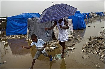 A woman and a child walk at a homeless earthquake survivors camp during heavy rains in Port-au-Prince, Friday, March 19, 2010. A 7.0-magnitude earthquake hit Haiti on Jan. 12, killing and injuring thousands and leaving more than a million people living in makeshift camps. (AP Photo/Ramon Espinosa)