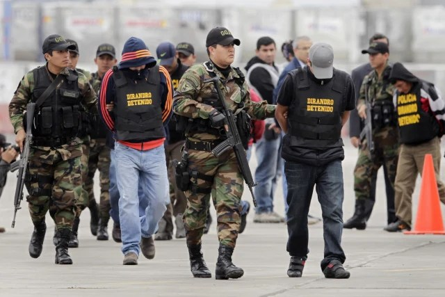 Image: Mexicans suspected of trying to smuggle 7.6 tonnes of cocaine to Europe are escorted by police officers after their arrival to the police airport in Lima