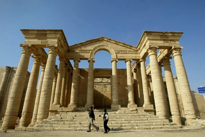 Image: Iraqi children run in front of a temple in the historic city of Hatra in 2002