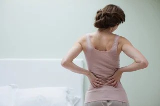 Image: A woman rubs her lower back